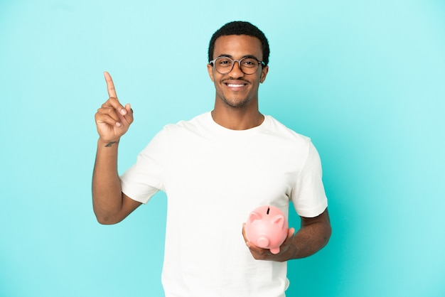 Афро-американский красавец держит копилку на синем фоне, указывая на отличную идею