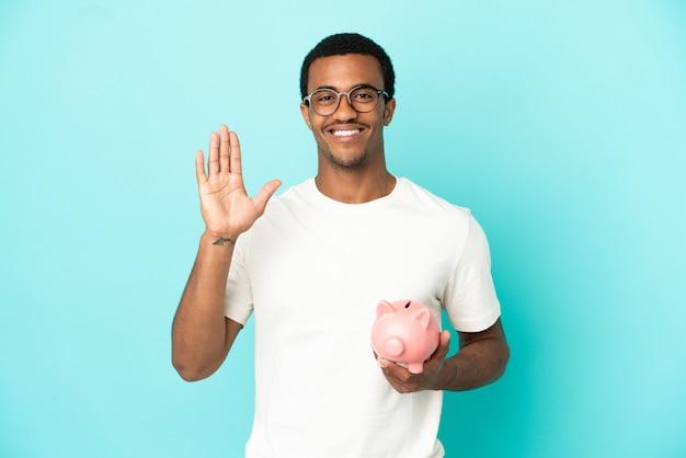 격리된 파란색 배경 위에 돼지 저금통을 들고 행복한 표정으로 손으로 경례하는 아프리카계 미국인 잘생긴 남자