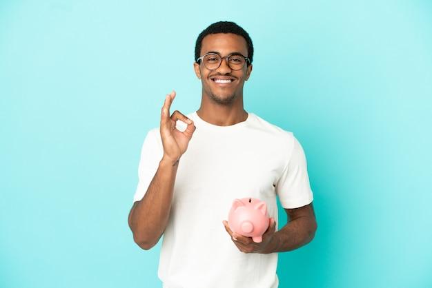 손가락으로 확인 표시를 보여주는 고립 된 파란색 배경 위에 돼지 저금통을 들고 아프리카 계 미국인 잘 생긴 남자