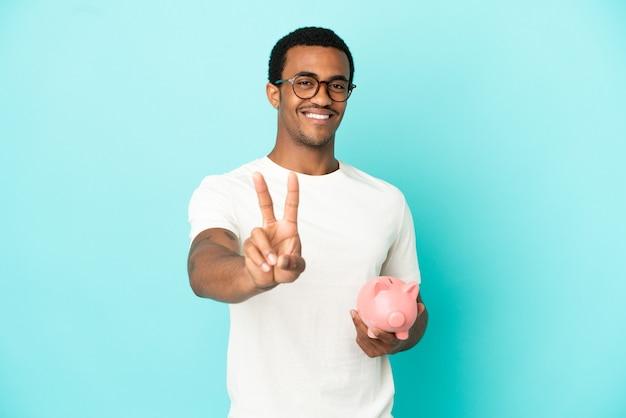 Афро-американский красавец, держащий копилку на синем фоне, улыбается и показывает знак победы