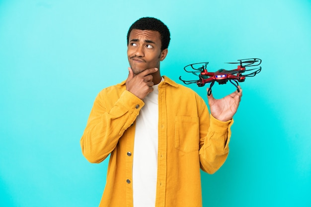 African american handsome man holding a drone over isolated blue background having doubts and thinking