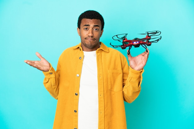 African american handsome man holding a drone over isolated blue background having doubts while raising hands