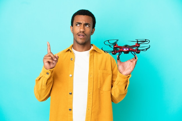 African american handsome man holding a drone over isolated blue background thinking an idea pointing the finger up
