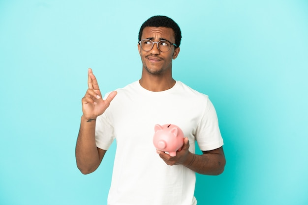 African american handsome man holding a piggybank over isolated blue background with fingers crossing and wishing the best