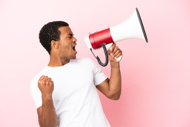 African american handsome man on isolated pink background shouting through a megaphone to announce something in lateral position