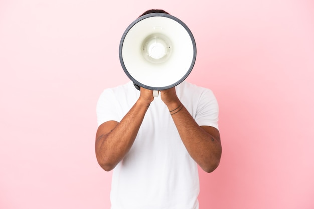 African american handsome man on isolated pink background shouting through a megaphone to announce something