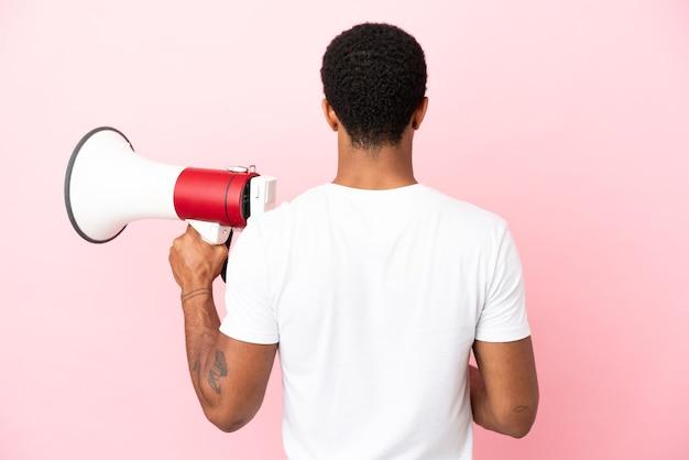 Афро-американский красавец на изолированном розовом фоне, держащий мегафон и в задней позиции