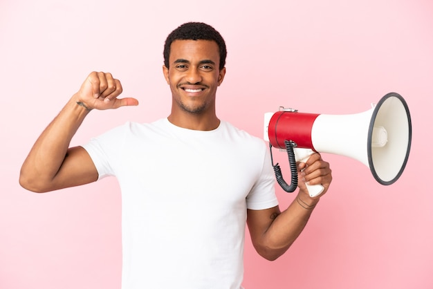 고립된 분홍색 배경에 있는 아프리카계 미국인 잘생긴 남자는 확성기를 들고 자랑스럽고 자기 만족