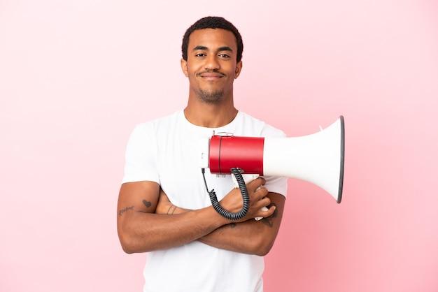 Афро-американский красавец на изолированном розовом фоне держит мегафон и улыбается
