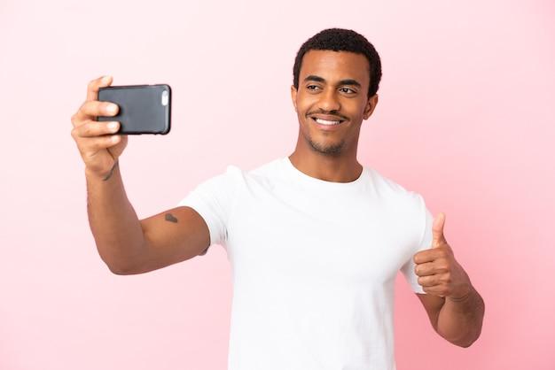 Афро-американский красавец на изолированном розовом фоне, делая селфи с мобильным телефоном