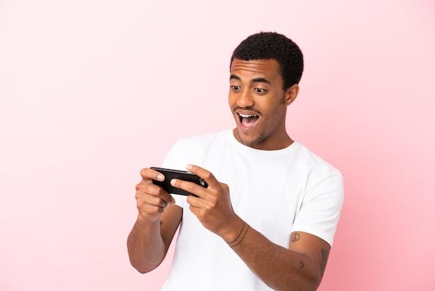 Афро-американский красавец на изолированном розовом фоне, играя с мобильным телефоном