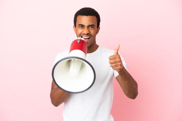 Афро-американский красавец на изолированном розовом фоне кричит в мегафон, чтобы объявить что-то и с большим пальцем вверх