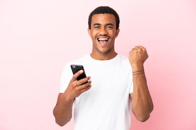 Афро-американский красавец на изолированном розовом фоне с помощью мобильного телефона и жест победы