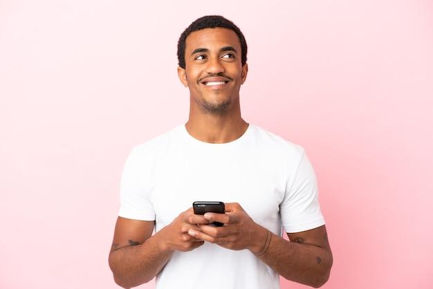 Афро-американский красавец на изолированном розовом фоне, используя мобильный телефон и глядя вверх