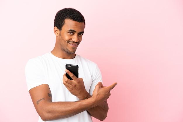携帯電話を使用して後ろ向きの孤立したピンクの背景にアフリカ系アメリカ人のハンサムな男