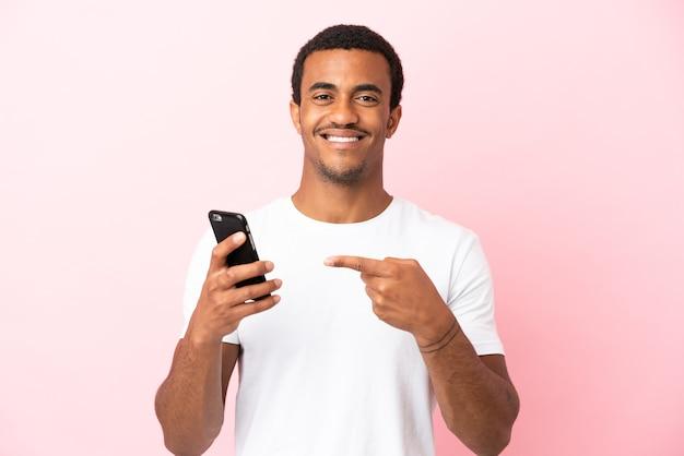 Афро-американский красавец на изолированном розовом фоне, используя мобильный телефон и указывая на него