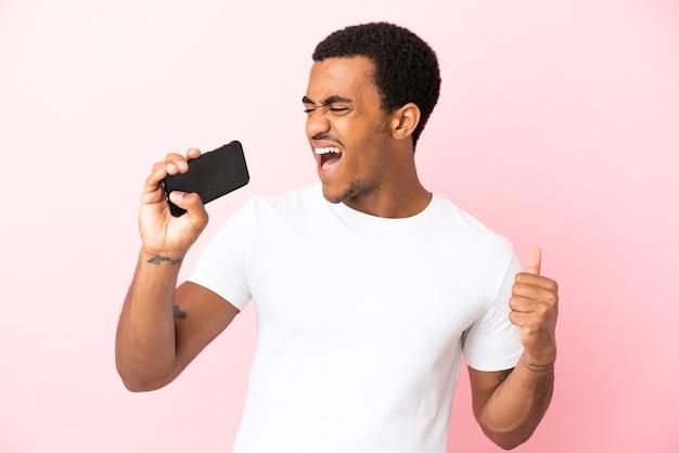 Афро-американский красавец на изолированном розовом фоне с помощью мобильного телефона и пения