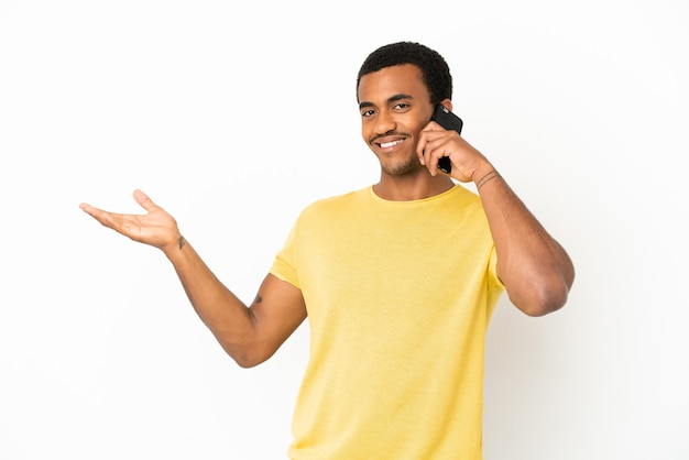 African american handsome man using mobile phone over isolated white background extending hands to the side for inviting to come