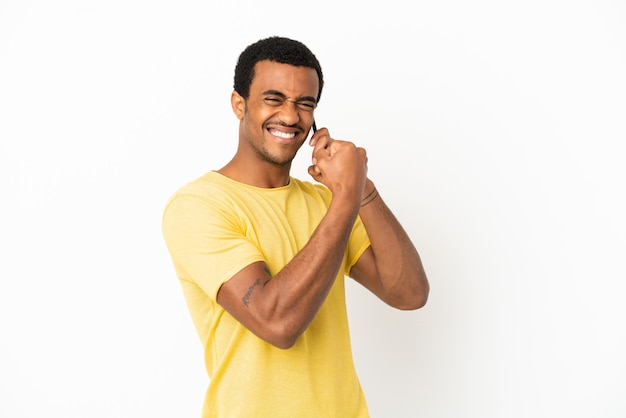 Афро-американский красавец с помощью мобильного телефона на изолированном белом фоне празднует победу