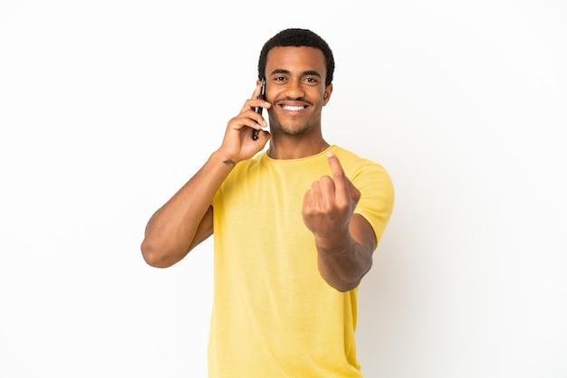 Афро-американский красавец, использующий мобильный телефон на изолированном белом фоне, делает приближающийся жест