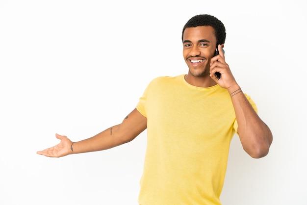 Афро-американский красавец, использующий мобильный телефон на изолированном белом фоне, протягивает руки в сторону, приглашая приехать
