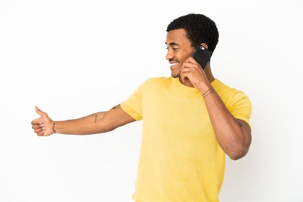 Афро-американский красавец, использующий мобильный телефон на изолированном белом фоне, жестом показывает палец вверх