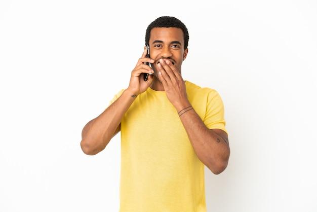 Афро-американский красавец, использующий мобильный телефон на изолированном белом фоне, счастливый и улыбающийся, прикрывая рот рукой