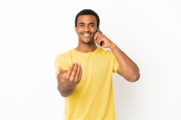 Афро-американский красавец с помощью мобильного телефона на изолированном белом фоне, приглашая прийти с рукой. счастлив что ты пришел