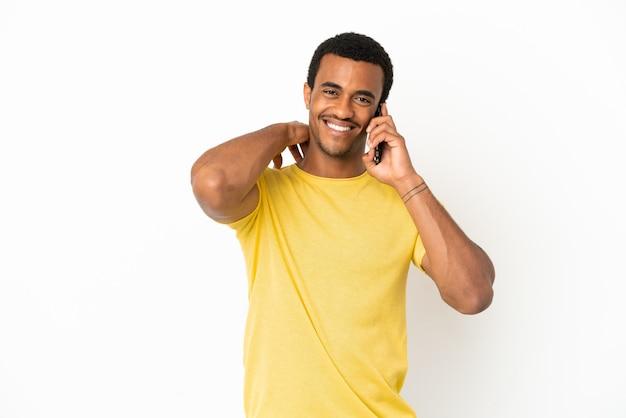 Афро-американский красавец с помощью мобильного телефона на изолированном белом фоне смеется