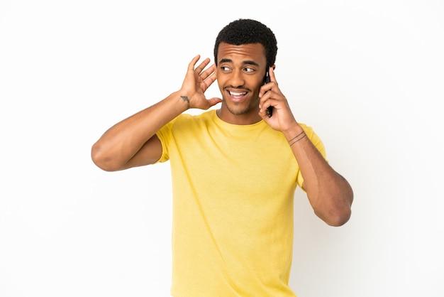 Афро-американский красавец с помощью мобильного телефона на изолированном белом фоне, слушая что-то, положив руку на ухо