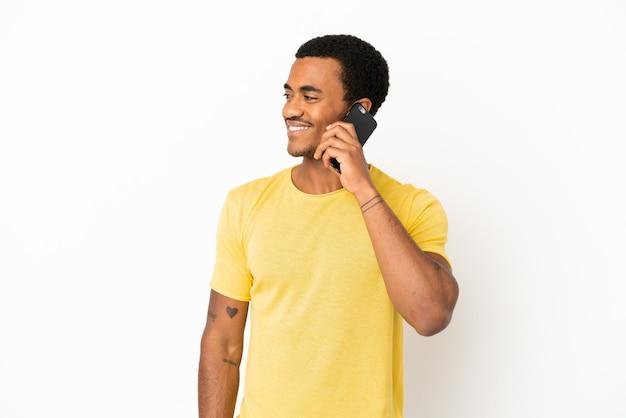 Афро-американский красавец, использующий мобильный телефон на изолированном белом фоне, глядя в сторону