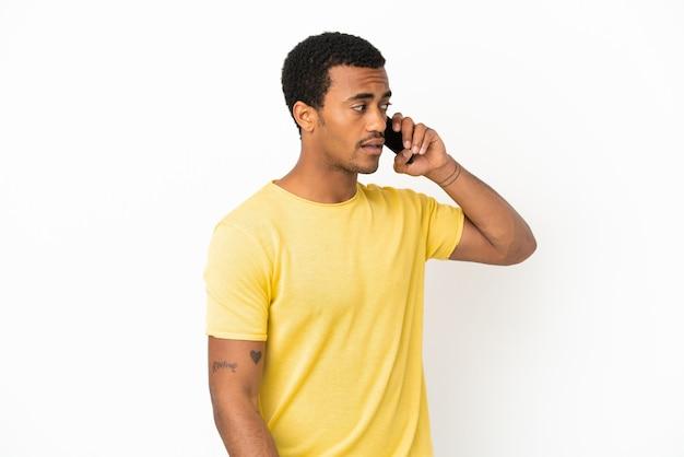Афро-американский красавец с помощью мобильного телефона на изолированном белом фоне, глядя в сторону