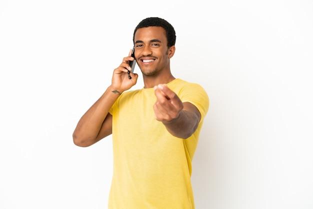 Афро-американский красавец с помощью мобильного телефона на изолированном белом фоне, делая денежный жест