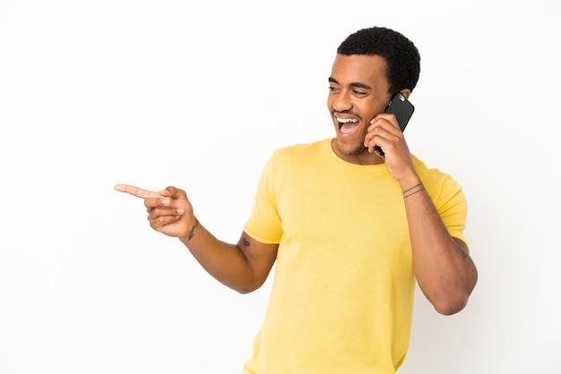 Афро-американский красавец, использующий мобильный телефон на изолированном белом фоне, указывая пальцем в сторону и представляя продукт