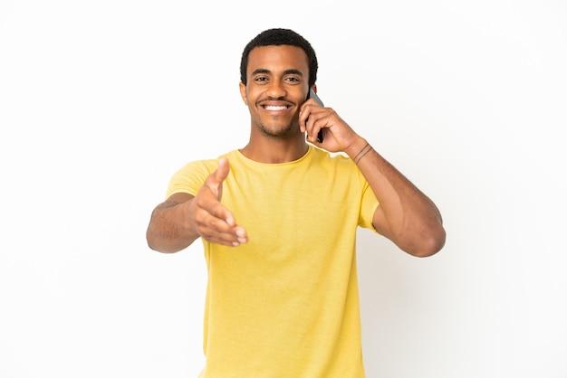 좋은 거래를 성사시키기 위해 악수하는 격리된 흰색 배경 위에 휴대전화를 사용하는 아프리카계 미국인 잘생긴 남자