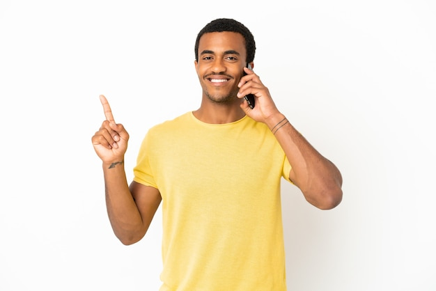 Афро-американский красавец, использующий мобильный телефон на изолированном белом фоне, показывает и поднимает палец в знак лучших