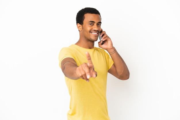 Афро-американский красавец, использующий мобильный телефон на изолированном белом фоне, показывает и поднимает палец