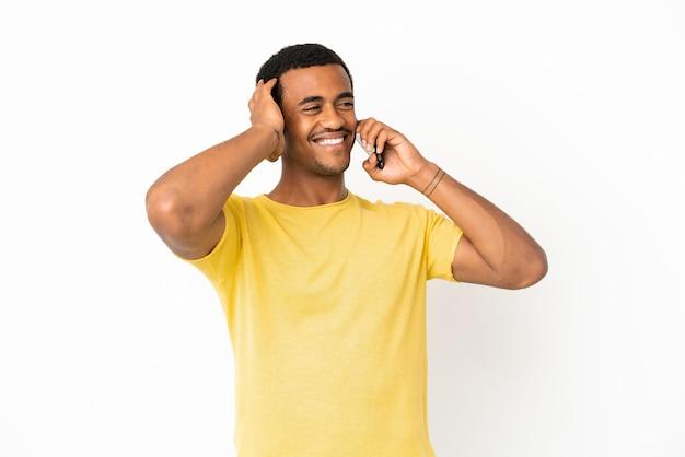 Афро-американский красавец, использующий мобильный телефон на изолированном белом фоне, много улыбаясь
