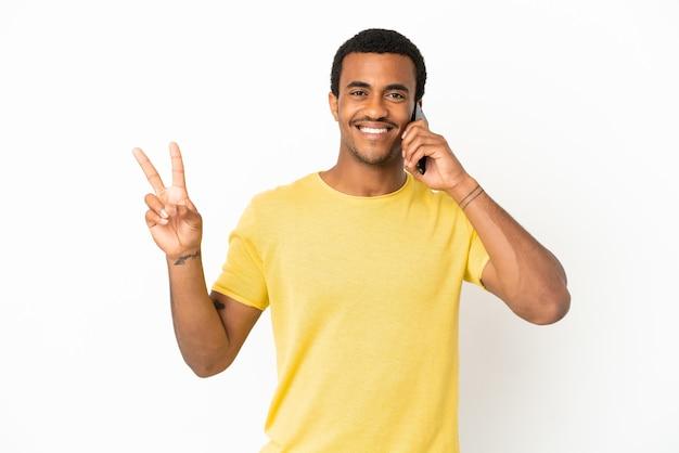 Афро-американский красавец с помощью мобильного телефона на изолированном белом фоне улыбается и показывает знак победы