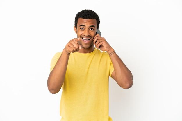Афро-американский красавец, использующий мобильный телефон на изолированном белом фоне, удивился и указал вперед