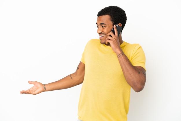 Афро-американский красавец с помощью мобильного телефона на изолированном белом фоне с удивленным выражением лица, глядя в сторону