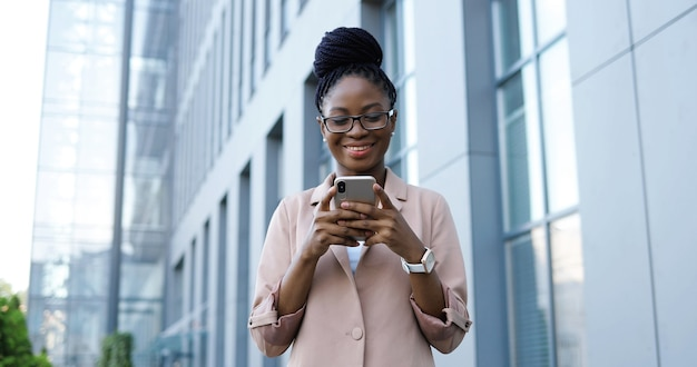 スマートフォンでタップしてスクロールするアフリカ系アメリカ人の幸せな若い実業家。屋外の携帯電話で女性のテキストメッセージメッセージ。ガジェットを使用し、チャットしながら笑顔の女性。