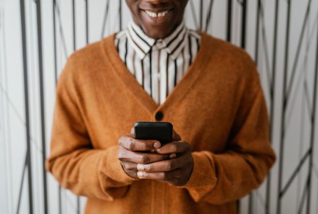 Afroamericano che tiene il suo telefono