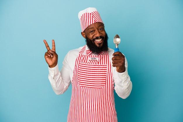 Афро-американский производитель мороженого человек, держащий совок мороженого на синем фоне, радостный и беззаботный, показывая пальцами символ мира.