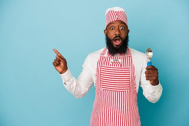 Афро-американский производитель мороженого мужчина держит совок мороженого на синем фоне, указывая в сторону
