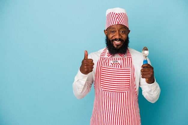 Афро-американский производитель мороженого мужчина держит совок мороженого на синем фоне улыбается и поднимает большой палец вверх