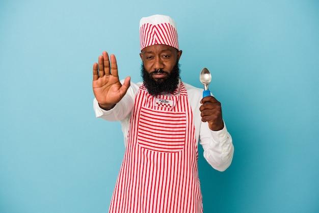 Афро-американский производитель мороженого человек, держащий совок мороженого на синем фоне, стоящий с протянутой рукой, показывая знак остановки, предотвращая вас.