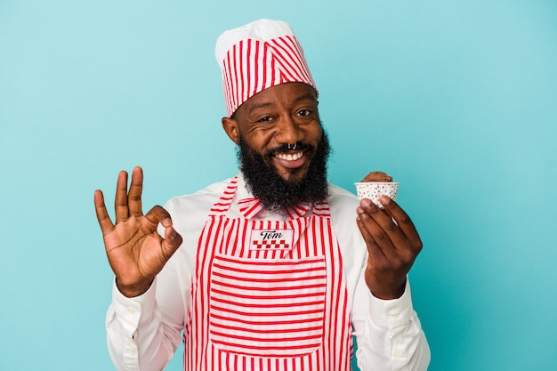 African american ice cream maker man holding an ice cream isolated on blue background cheerful and confident showing ok gesture.