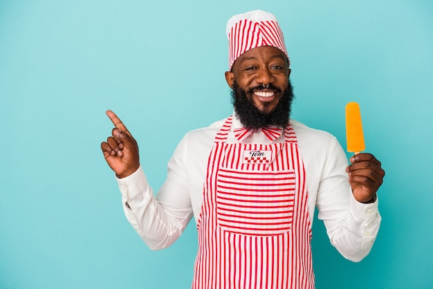African american ice cream maker man holding an ice cream isolated on blue background smiling and pointing aside, showing something at blank space.
