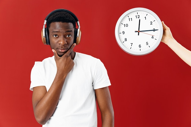 時計の赤い背景の横にある白いtシャツのヘッドフォンでアフリカ系アメリカ人